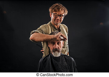 Hairdresser cuts senior citizen with a beard on a dark background in the studio