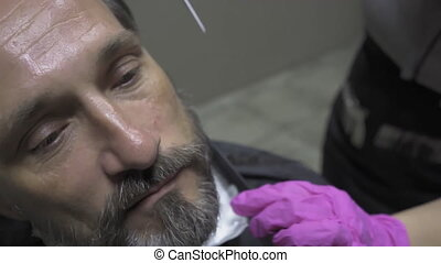 Hairdresser cuts the beard of a man at home during the ...