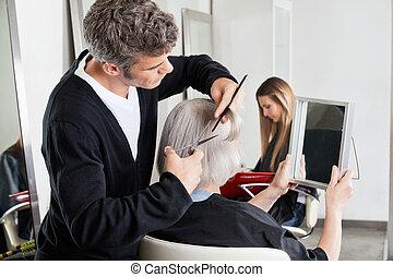 Hairdresser Cutting Client's Hair At Salon