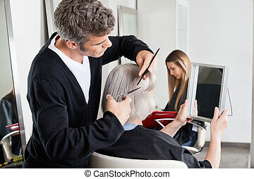 Hairdresser Cutting Client's Hair At Salon
