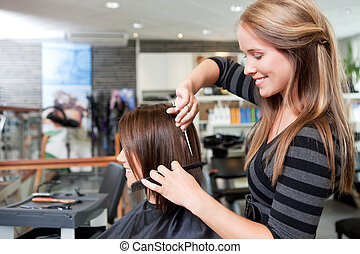 Hairdresser cutting client's hair in beauty salon.