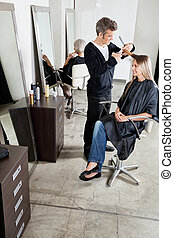 Hairdresser Cutting Client's Hair In Parlor - Male...