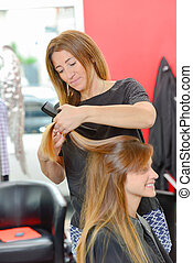 Hairdresser cutting hair of female client
