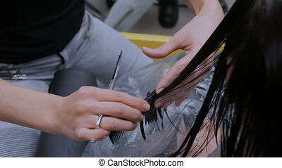 Hairdresser cutting hair of woman client