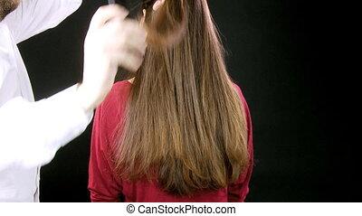 Hairdresser cutting long hair
