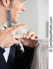 Hairdresser Cutting Senior Woman's Hair At Salon
