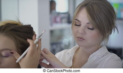 Hairdresser does hairstyle of lady while artist puts make-up, in beauty salon.