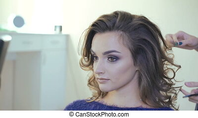 Hairdresser doing curles for smart woman in the studio in...