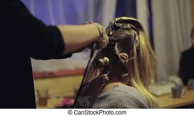 Hairdresser doing hairstyle for blonde woman