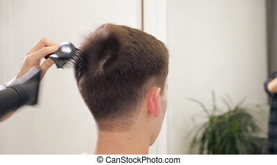 Hairdresser dries hair adult man hair dryer in the barber...