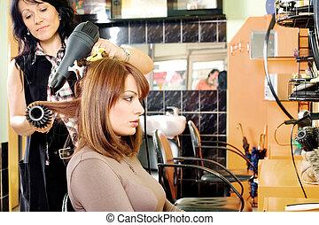 hairdresser dries hair in a hair salon