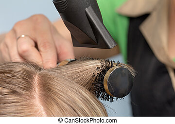 Hairdresser dries the hair in a beauty salon