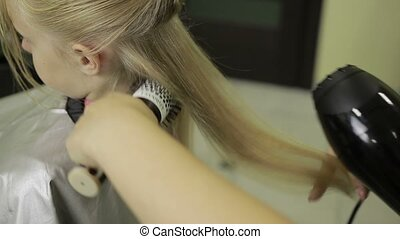Hairdresser drying hair with hair dryer and brush -...
