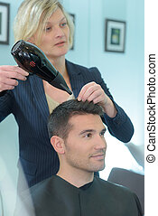 Hairdresser drying male customer's hair