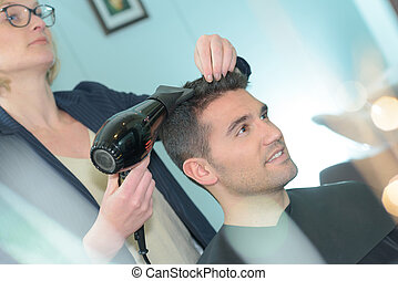 Hairdresser drying man's hair