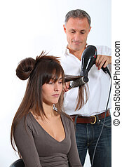 Hairdresser drying woman's hair