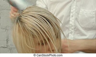 Hairdresser drying woman's hair using hair dryer....