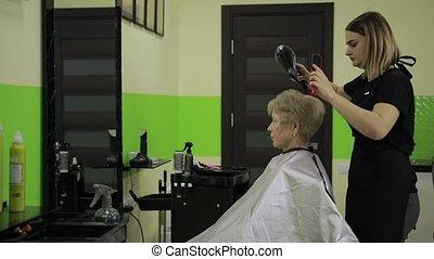 Hairdresser drying woman's hair using hair dryer -...