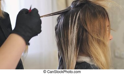 Hairdresser Dye the Hair, he Separates the Strands of Hair Comb Apply Foil and Color Hair Dye Blonde Girl Came to a Beauty Salon Hair Pinned Purple Barrette.