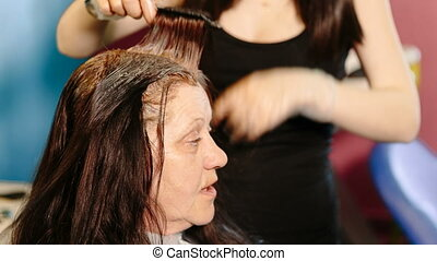Hairdresser dye the hair of the old woman.
