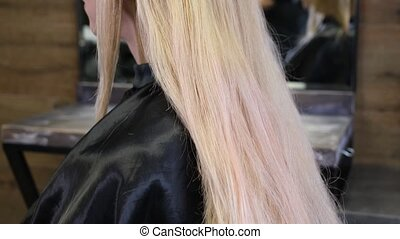 Hairdresser dyes blonde client hair in a beauty salon. Studio hairdresser. Paint application process