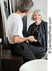 Hairdresser Examining Customer's Hair At Parlor
