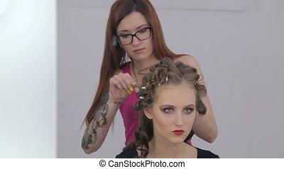 Hairdresser finishing hairstyle for teen girl