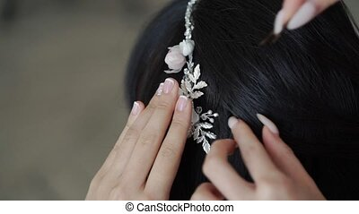 Hairdresser fixing hair decoration accessories to brunette...
