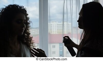 Hairdresser fixing woman with curly hair with hairspray. Silhouettes of girls against the window in the apartment.