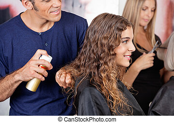 Hairdresser Fixing Woman's Hair With Spray