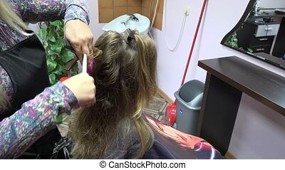 hairdresser giving a new haircut to female customer at parlor. Handheld. 4K