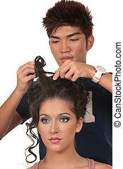 Hairdresser - Hair dresser fixing model's hair