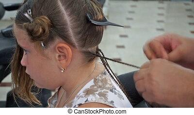 Hairdresser hands weaving a dreadlocks for girl