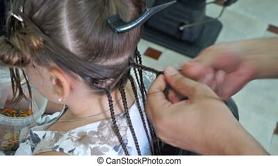 Hairdresser hands weaving a dreadlocks for little girl
