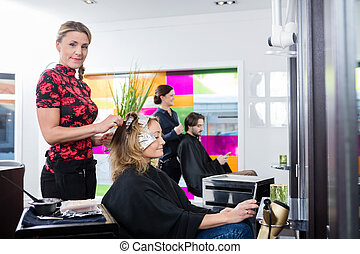 Hairdresser Highlighting Customer's Hair In Parlor