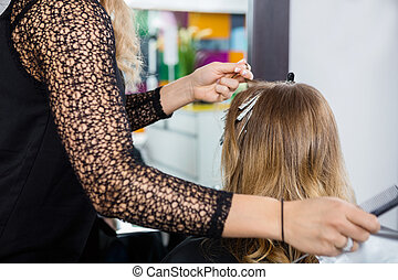 Hairdresser Highlighting Customer's Hair In Salon
