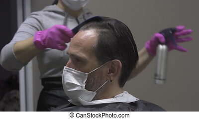Hairdresser in a protective mask professionally applying ...