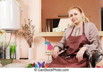 Hairdresser in chair - Blonde hairdresser sitting in chair...