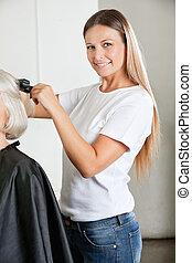 Hairdresser Ironing Female Client's Hair