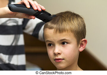 Hairdresser is cutting hair of a child boy in barber shop