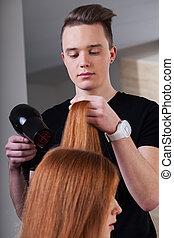 Hairdresser is drying customer hair