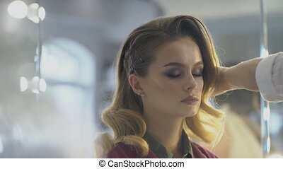 Hairdresser is spraying hairspay on hairstyle of beautiful lady in beauty salon.