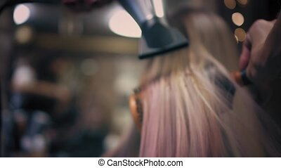 Hairdresser is strighten woman's long pink blonde hair with...