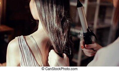 Hairdresser makes hair brunette girl