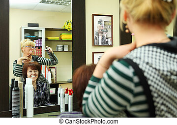 Hairdresser makes hair styling for woman by hair spray in beauty salon; reflection in mirror