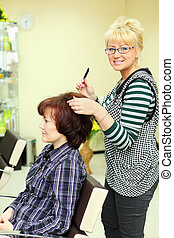 Hairdresser makes hair styling for woman by rake-comb and looks at camera in beauty salon