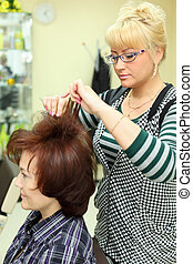 Hairdresser makes hair styling for woman by rake-comb in beauty salon