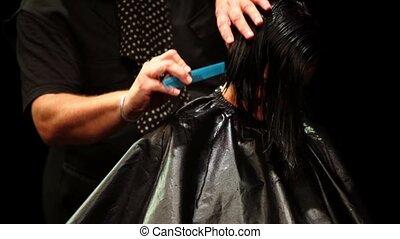 Hairdresser makes hairdo for black hair model, closeup view