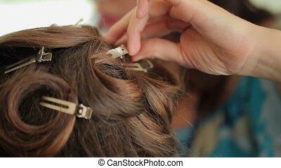 Hairdresser makes hairstyle closeup shot