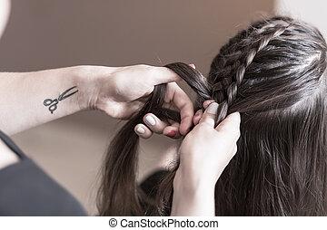 Hairdresser making a braid on long hair